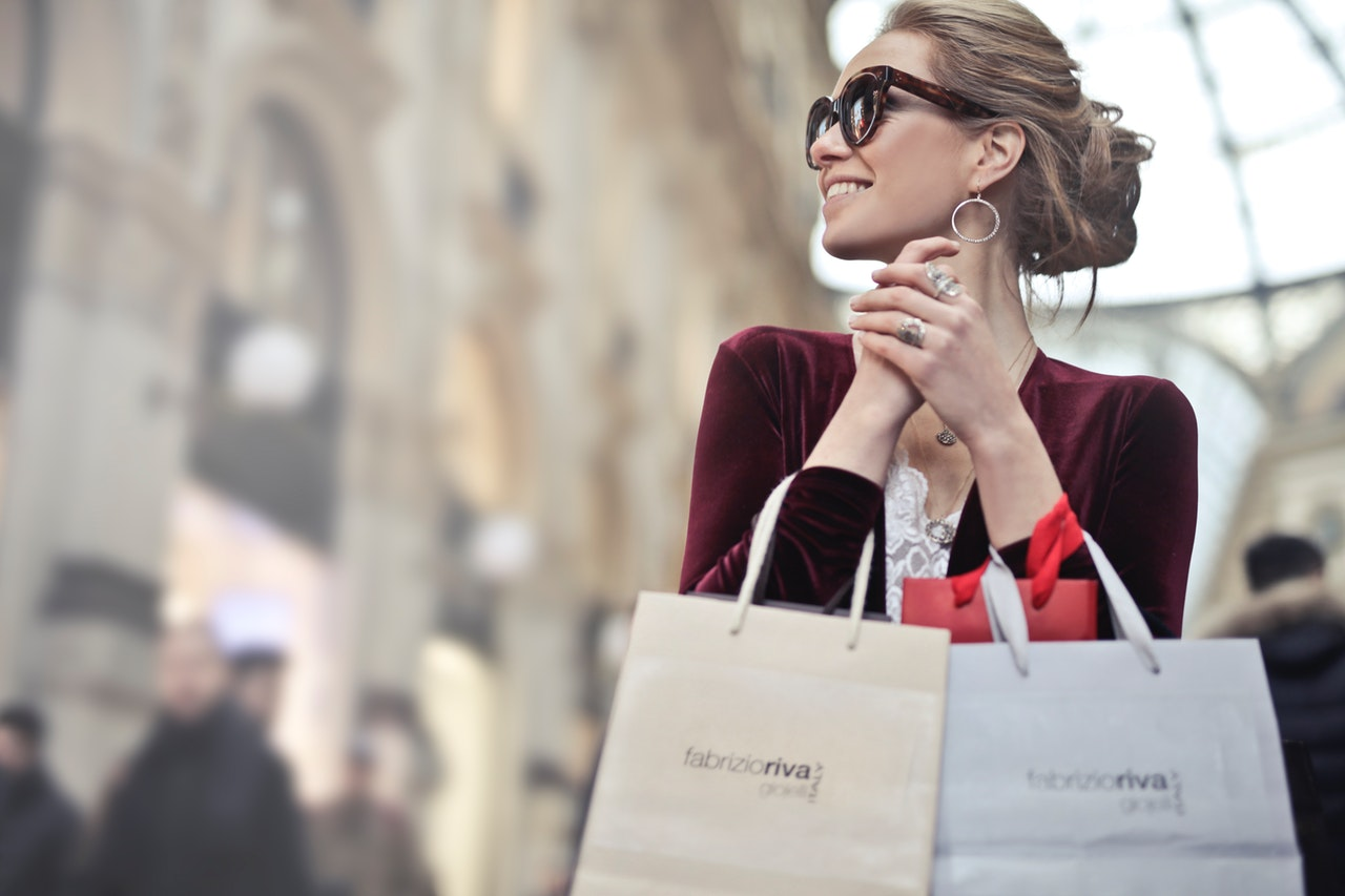woman-holding-two-white-and-beige-shopping-paper-bags-in-974911