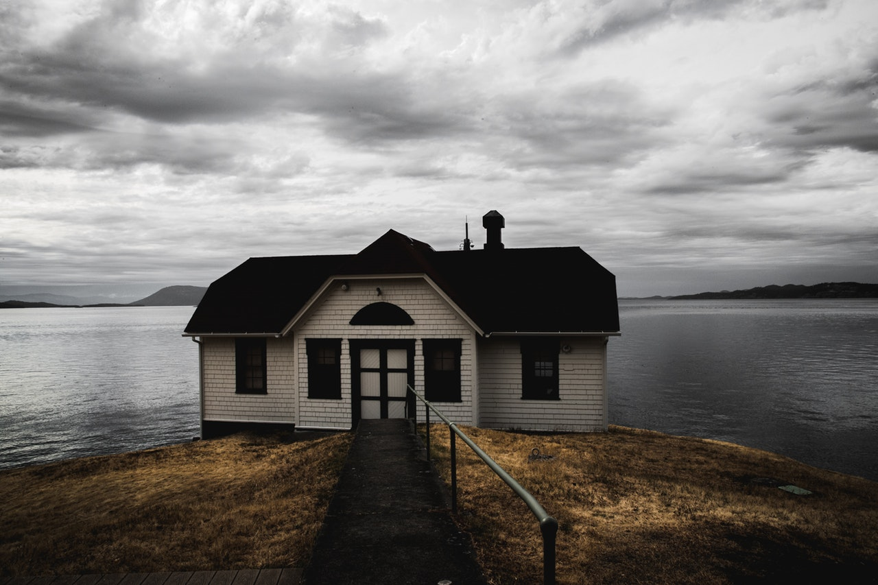 white-and-brown-wooden-house-near-calm-body-of-water-under-2479655